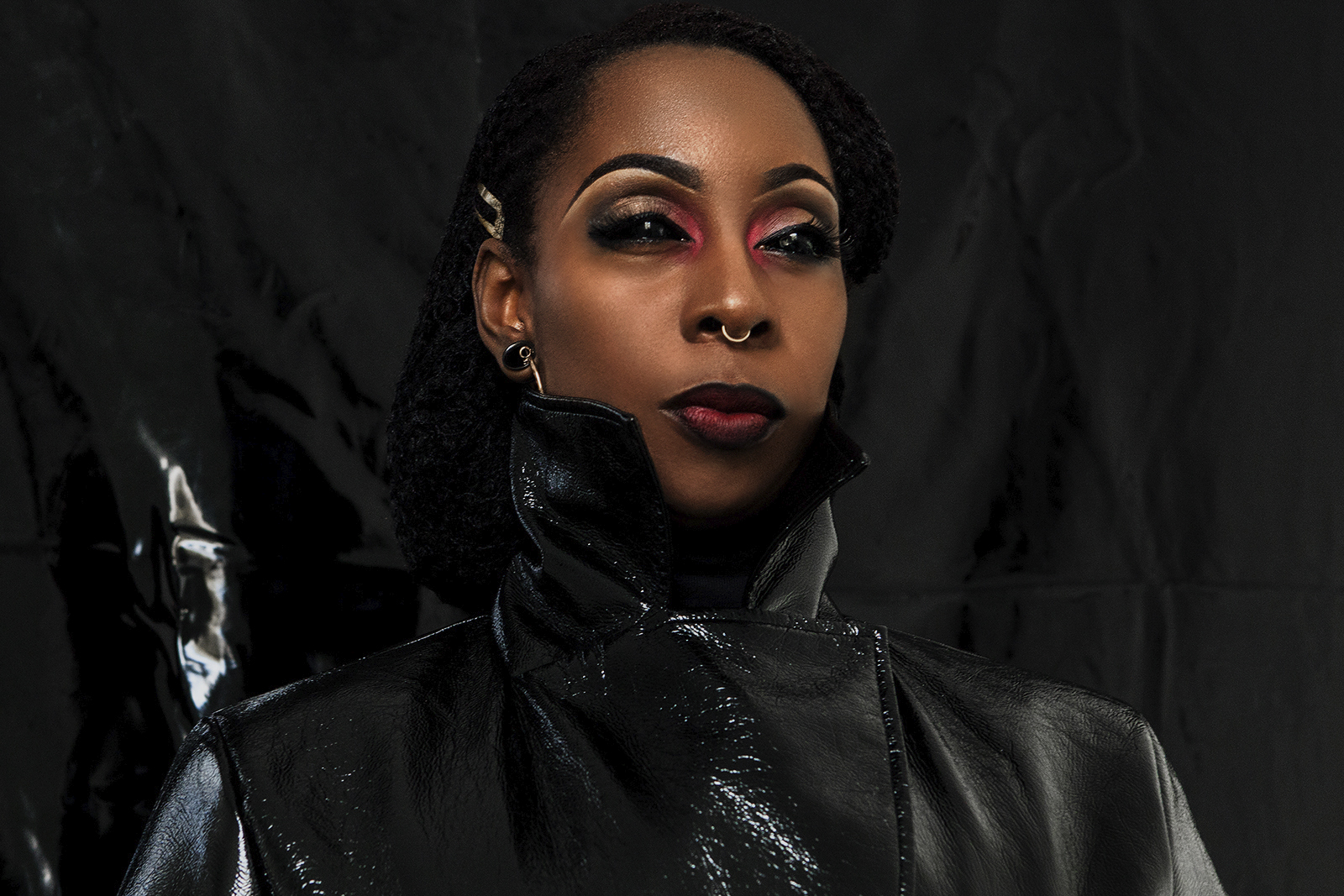 Promotional image for new performance Black on Black: 24R, featuring artist Zinzi Minott wearing black shiny coat and powerful make up, photo by Kofi Paintsil