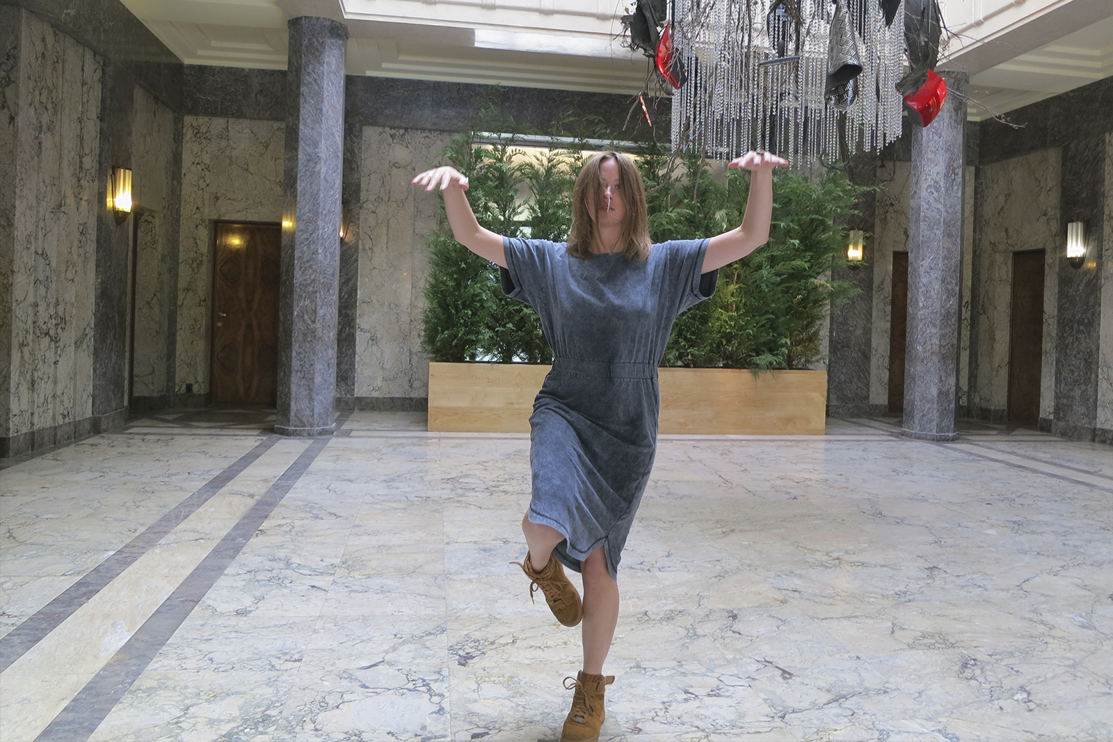 Janine Harrington in the middle of performing a movement sequence in the foyer of a gallery space.