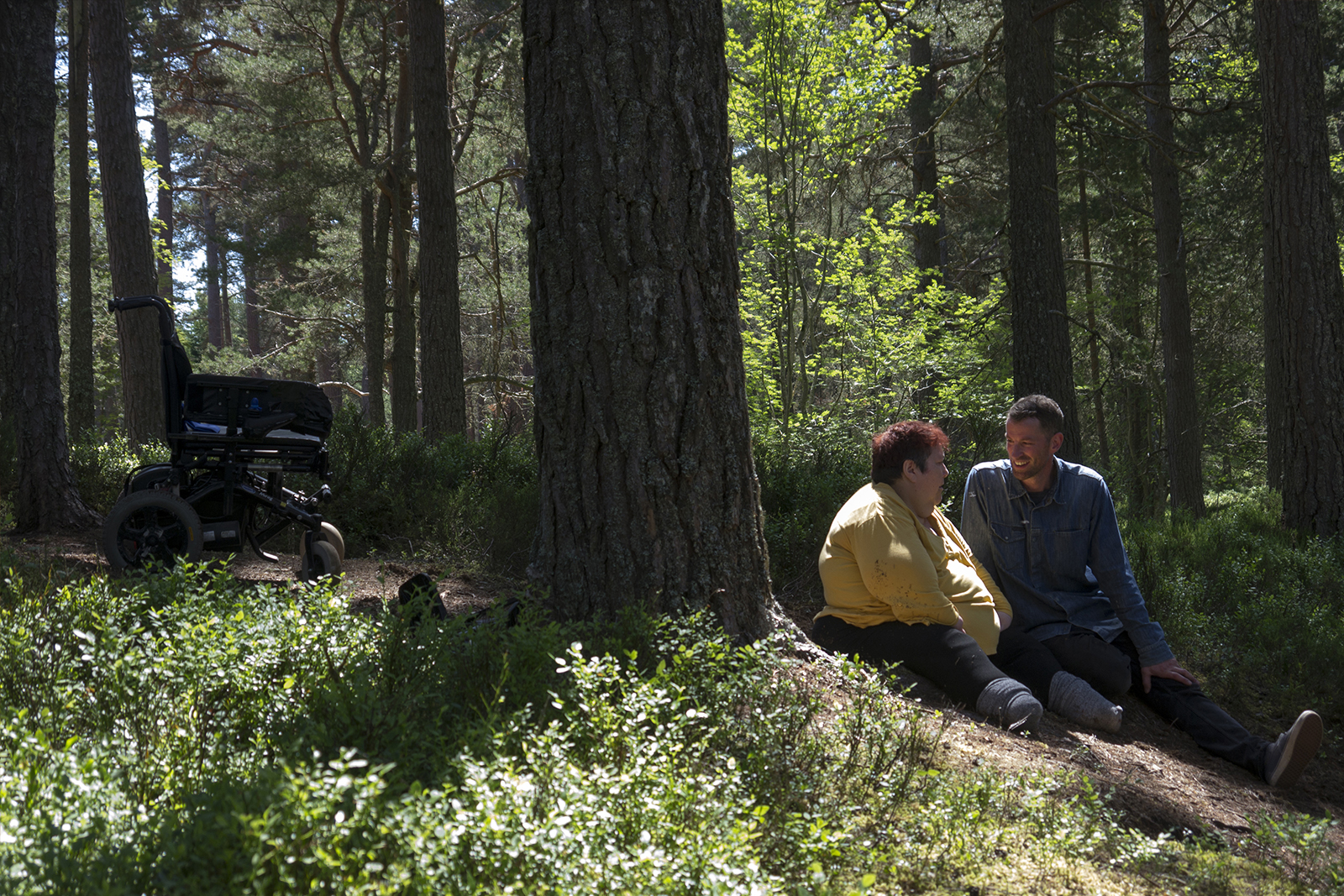Robbie Synge and Julie Cleves sitting down in a forest, smiling at one another. A wheelchair is visible in the left hand side of the frame.