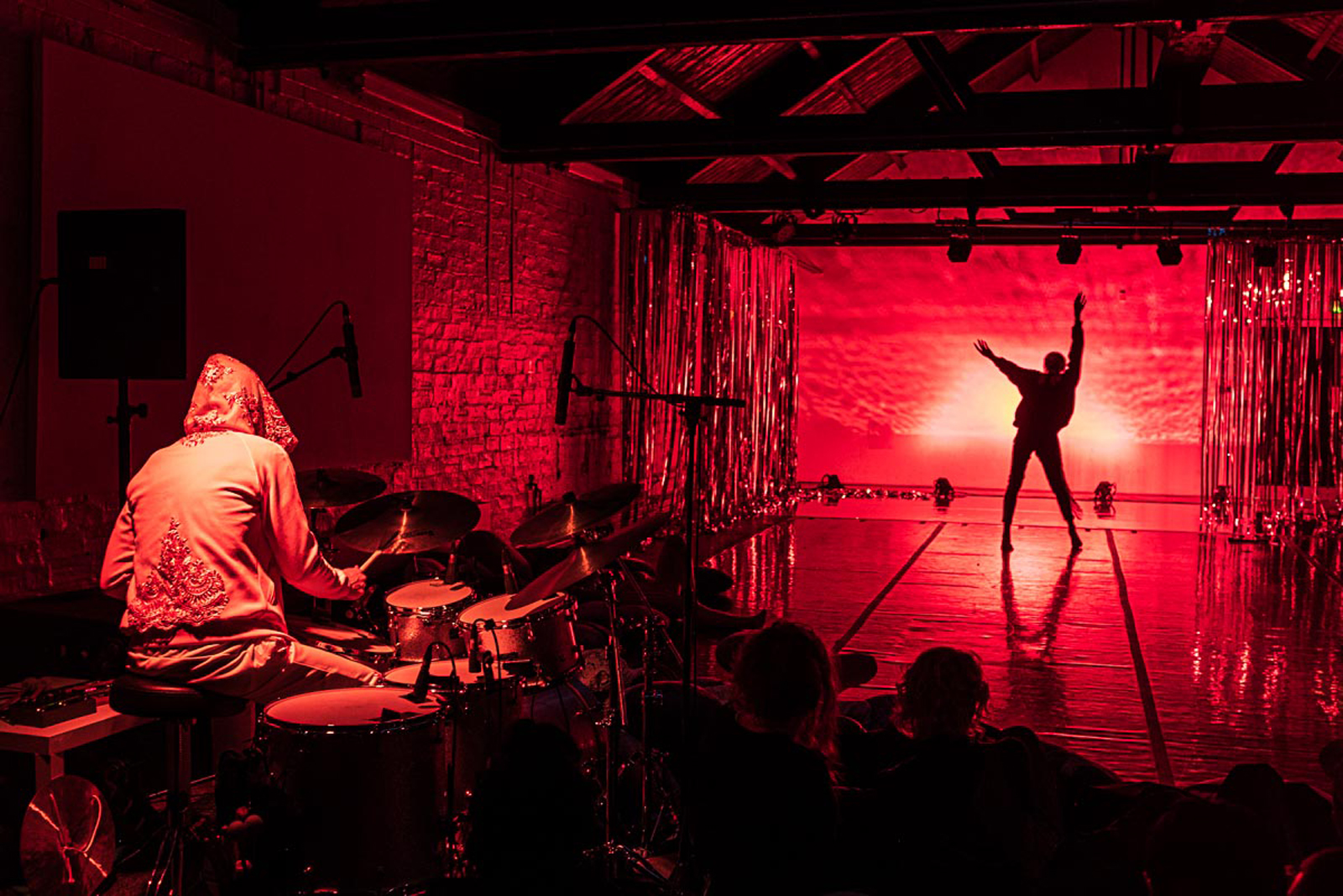 Photograph taken at performance of Spirit Compass at Tramway, Glasgow. Image features performer and musician performing simultaneously to a small, intimate sized audience. Photo by Brian Hartley.