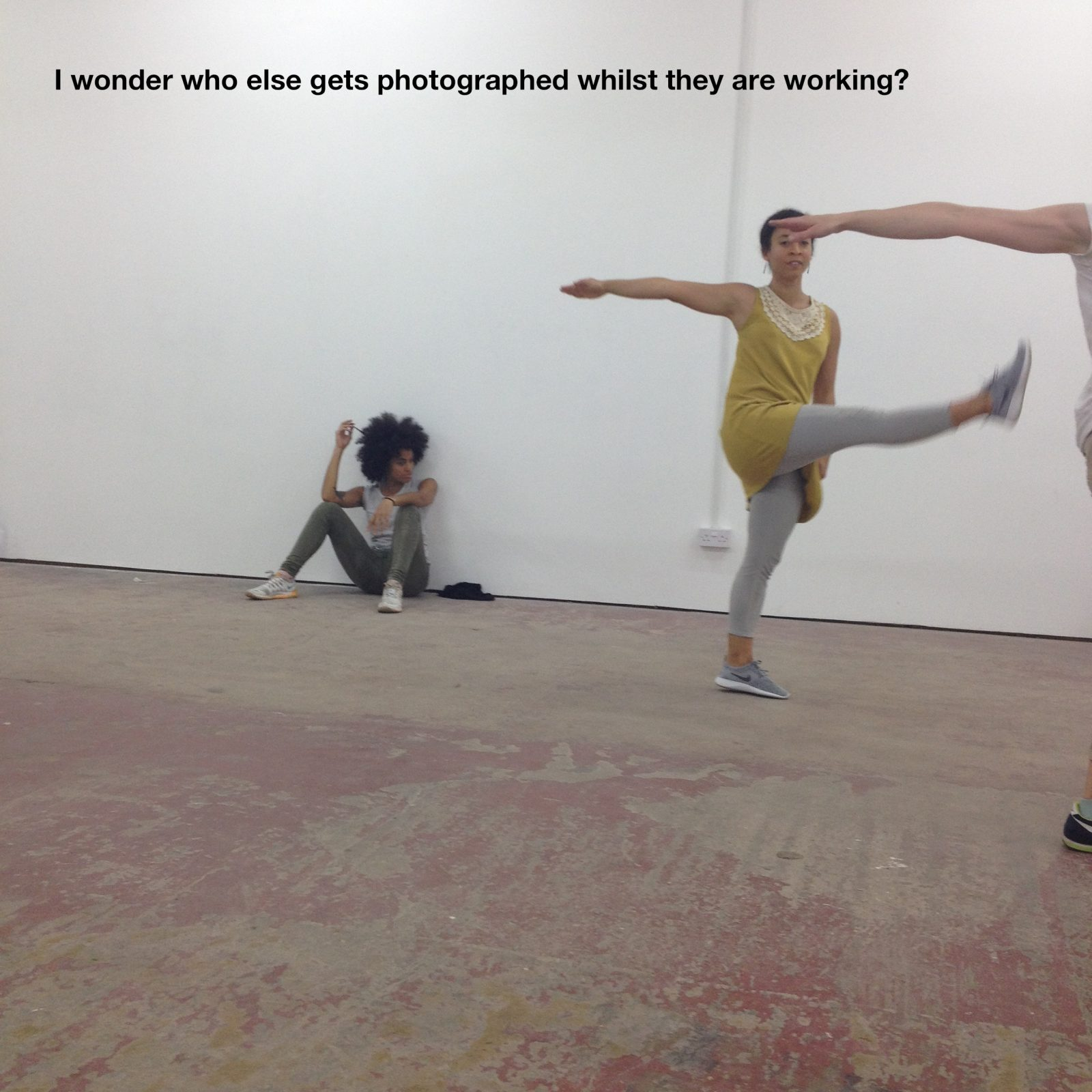Dancers mid movement in a white gallery space. A person sits on the floor behind the dancers. Black text appears at the top of the image. It reads: 'I wonder who else gets photographed whilst they are working?'
