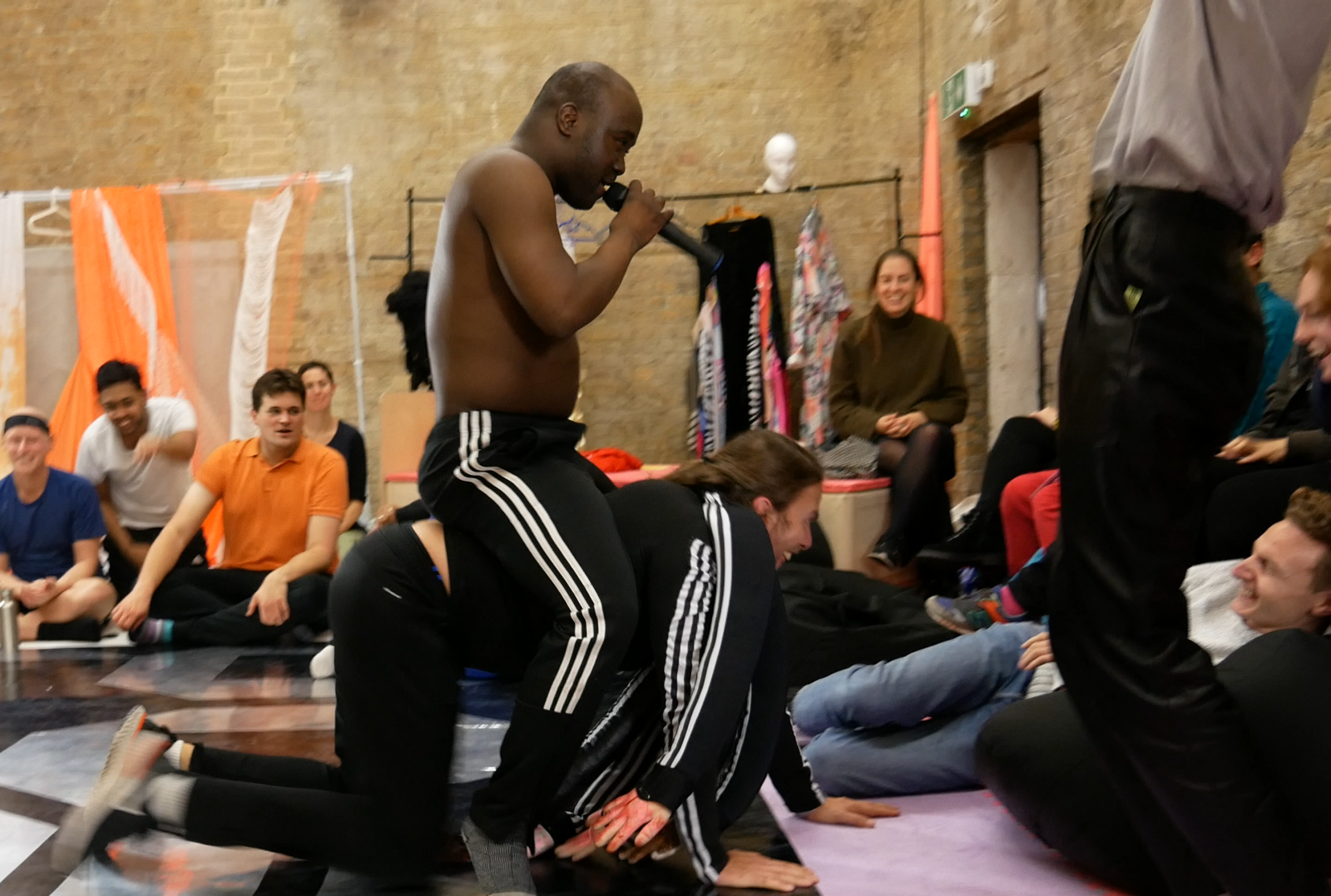 Freestylers performing to a busy crowd. One male performer is holding a microphone to their face whilst they sit on the back of another performer who is smiling to the crowd. They are both wearing black tracksuits.